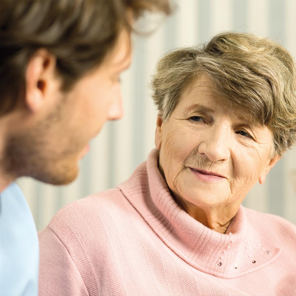 Eine ältere Frau hört interessiert zu, was VAGET zur gerontopsychiatrischen Betreuung und Pflege anzubieten hat.