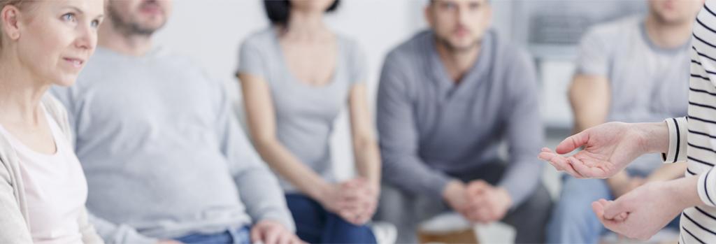 Eine Gruppe von Pflegerinnen und Betreuern wird beraten im gerontopsychiatrischen Kontext.